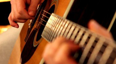 stock-footage-man-playing-guitar-close-up